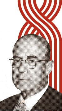 Josep Alsina i Bofill. Al fons, logotip del Desè Congrés de Metges i Biòlegs de Llengua Catalana que ell va presidir i que tingué lloc a Perpinyà.